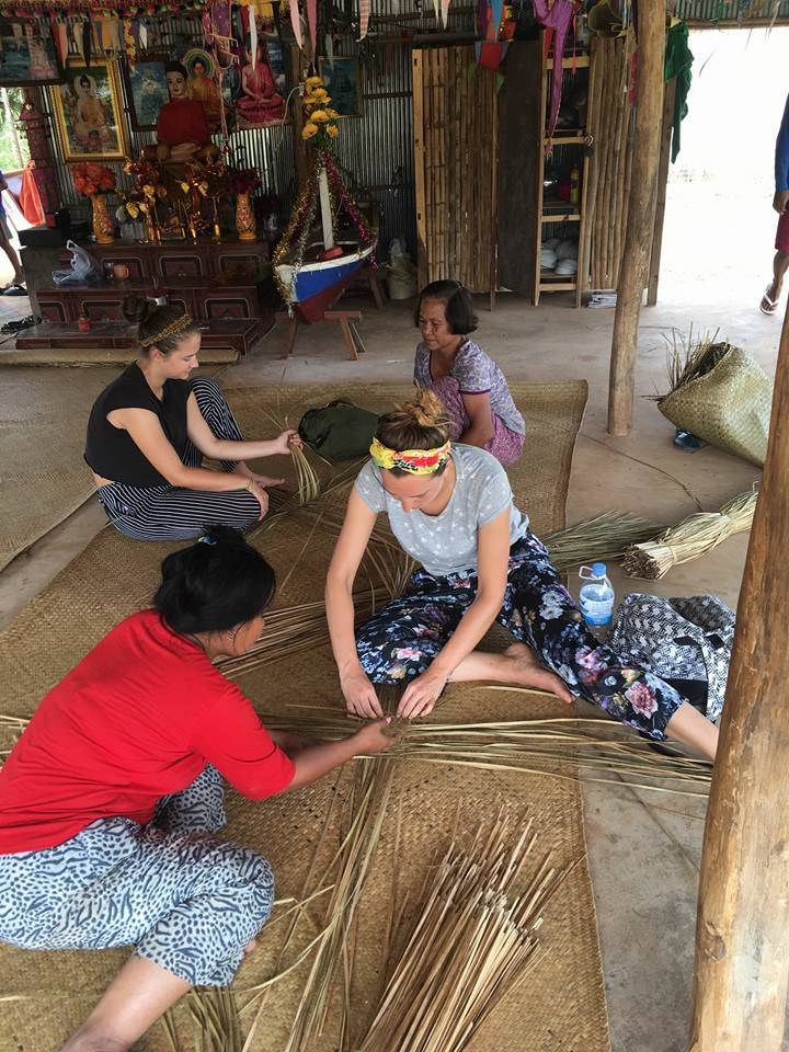 Local women supervise as visitors make mats; all sit on the floor
